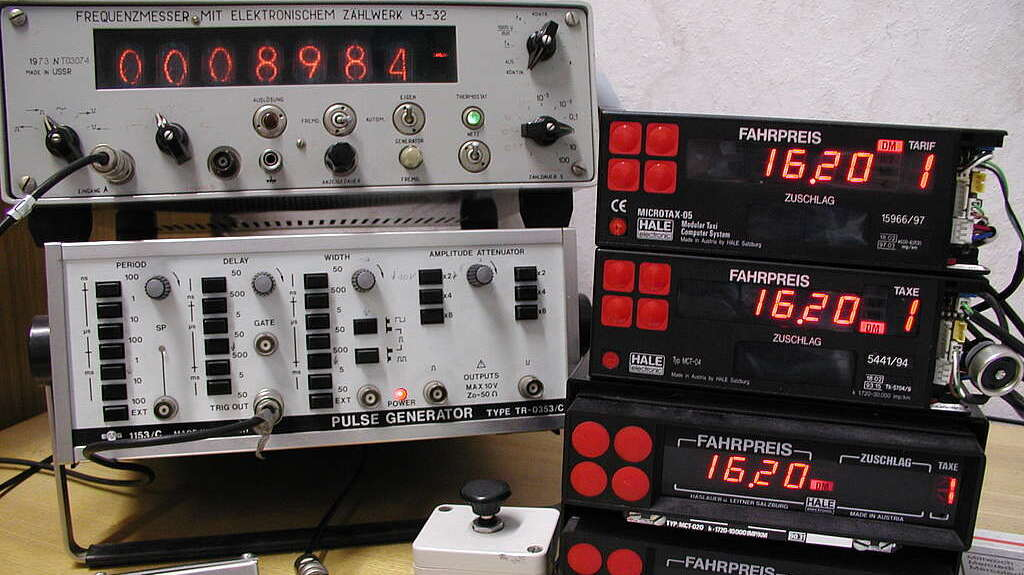 Ein Messgerät mit roter Leuchtanzeige sowie mehrere Taxameter übereinander gestapelt