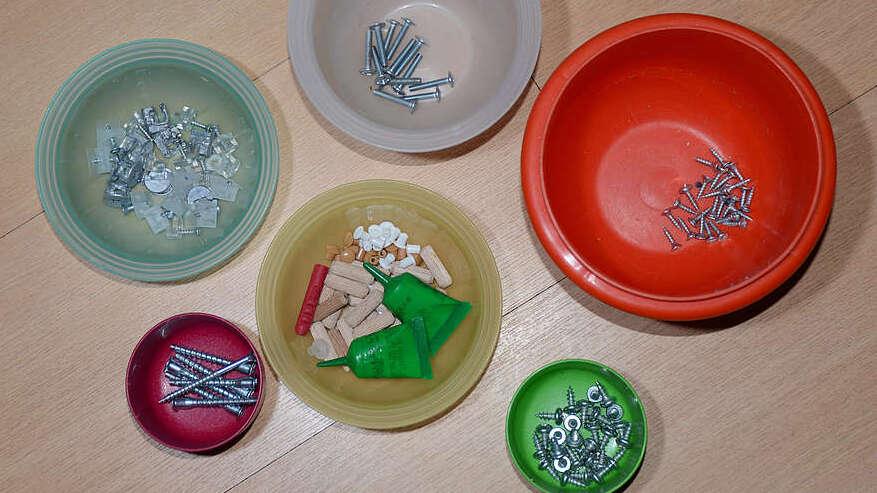 Verschiedene Kleinteile, wie Schrauben und Nägel in verschieden farbigen Schüsseln