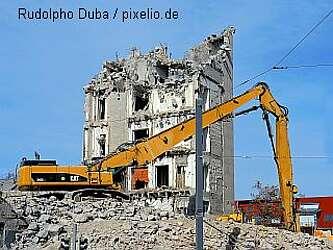 Abrissbagger auf einem Schutthaufen, im Hintergrund ein halb abgerissenes Haus