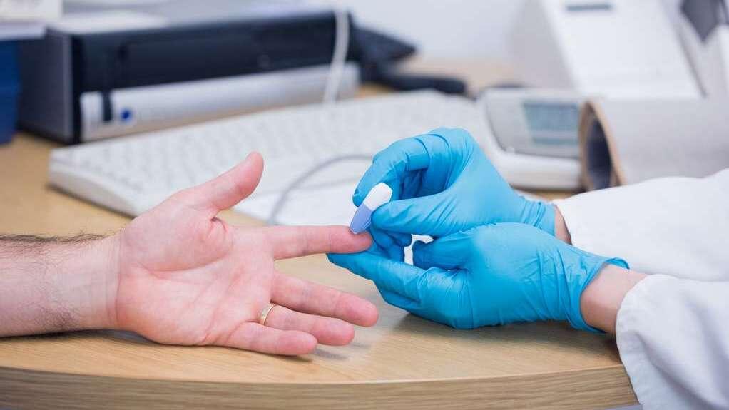 Hände eines Arztes mit hellblauen Gummihandschuhen beim Blutabnehmen am Finger eines Patienten, im Hintergrund verschwommen andere Messgeräte