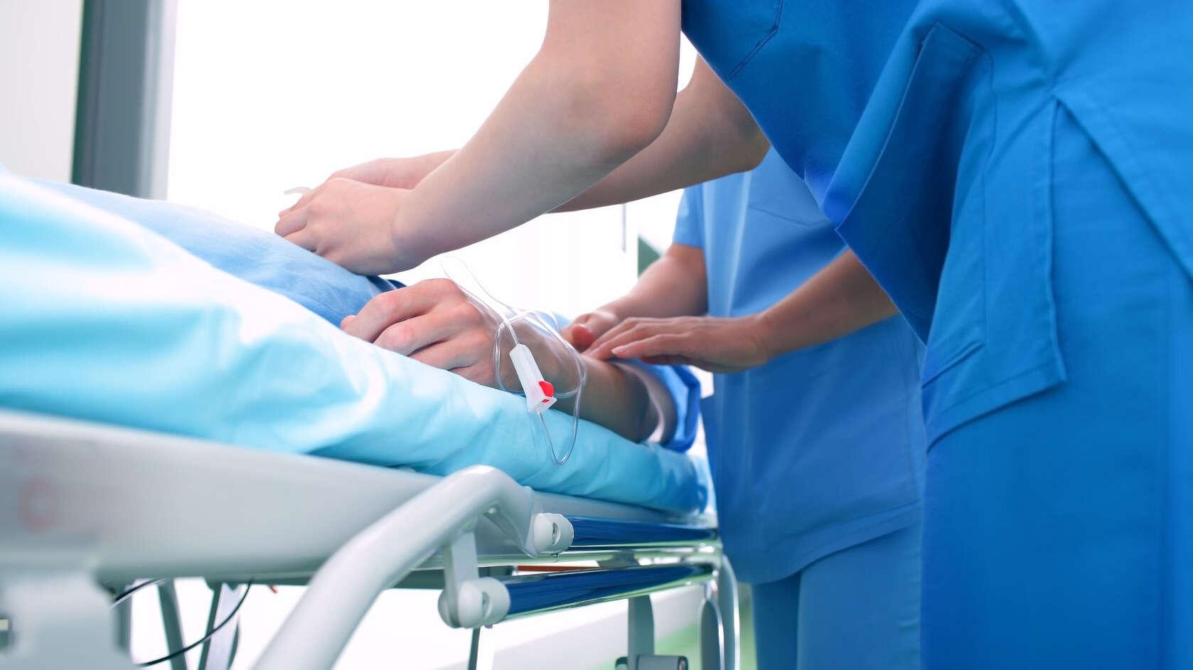 zwei Personen im blauen Kittel behandeln einen Patienten auf einer Krankentrage
