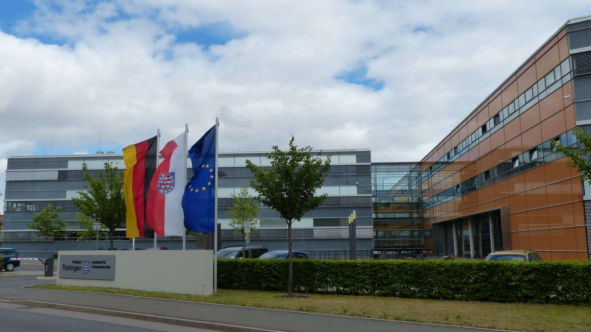 Blick auf die Einfahrt zum Dienstgebäude in Bad Langensalza mit Namensschild und Fahnen
