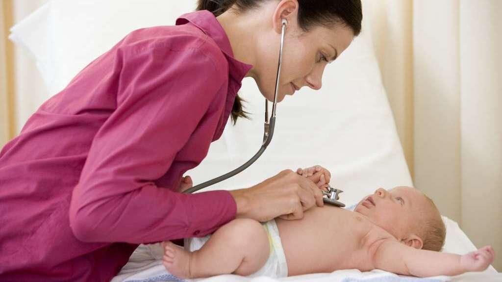 Ärztin mit pinkfarbenem Kittel untersucht ein Baby mit dem Stethoskop