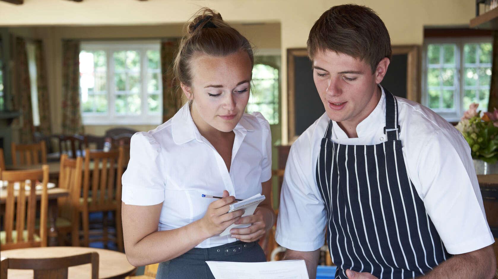 Eine junge Kellnerin und ein Kellner, er hält ein Blatt Papier in der Hand und sie sprechen darüber