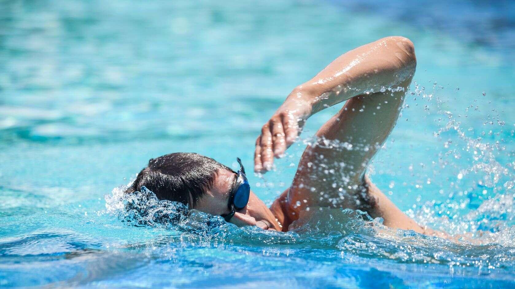 Ein Mann mit Schwimmbrille schwimmt in einem Schwimmbecken im Vorwärts-Kraulstil