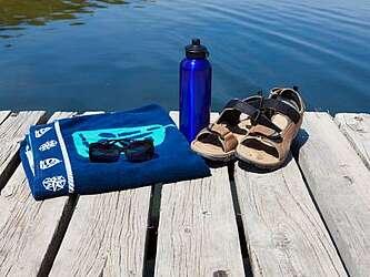 Teil eines Badestegs am See mit blauem Handtuch, Trinkflasche und Sandalen