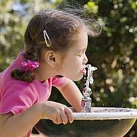 Kleines Mädchen trinkt an einem Wassersprudel am Trinkbrunnen, im Hintergrund grüne Blätter