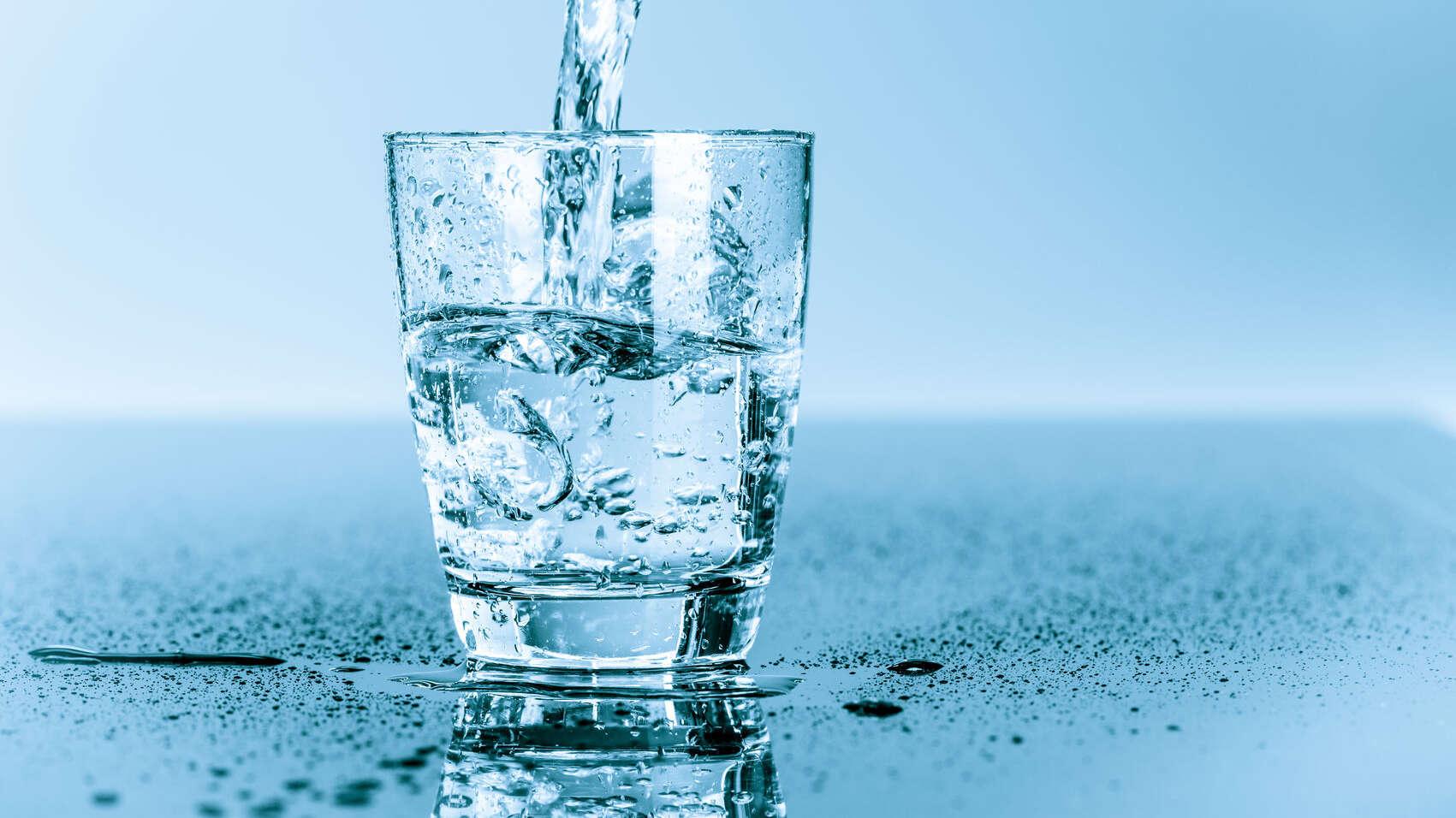 Wasserstrahl läuft in ein Glas