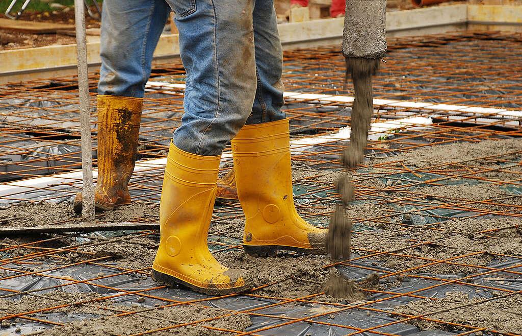 Flüsssiger Betonmörtel wird in ein Fundament gegossen, gelbe Gummistiefel