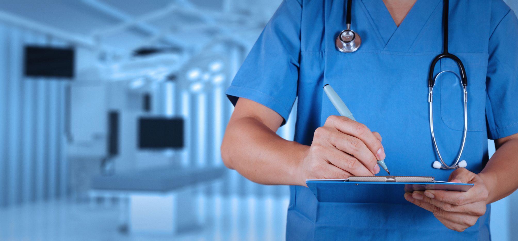 Mann im blauen Kittel mit Stetoskop um den Hals steht in einem medizinischen Behandlungsraum und schreibt etwas auf einem Block