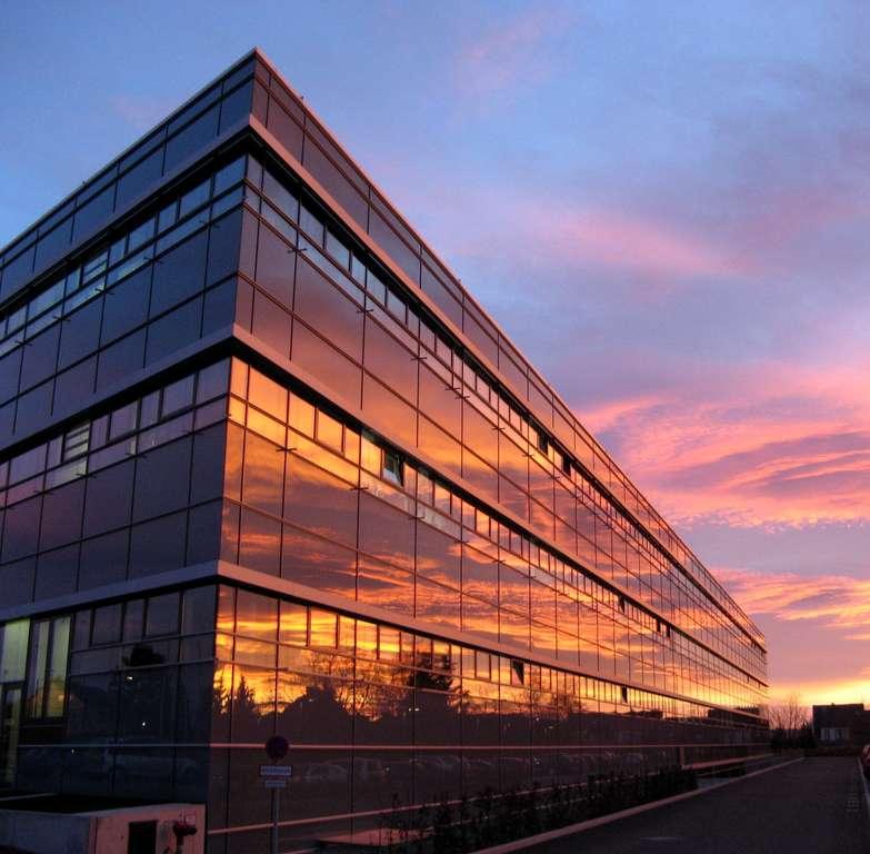 Dienstgebäude des TLV in Bad Langensalza mit Glasfassade, in der sich der Abendhimmel spiegelt