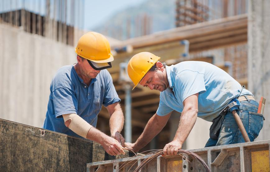 Zwei Bauarbeiter beim Biegen von Eisenstangen