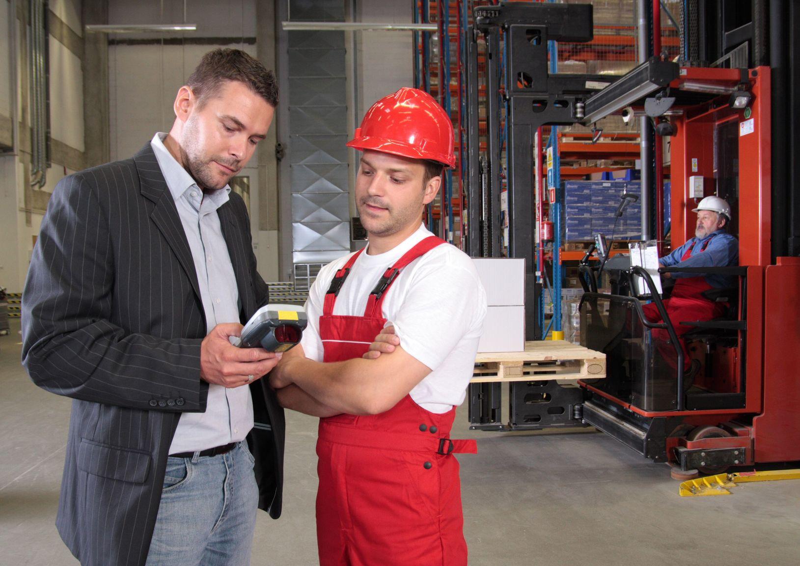 Vorgesetzter schaut zusammen mit Arbeiter in ein mobiles Gerät, beide stehen in einem Lager, im Hintergrund ein Mann mit Gabelstapler