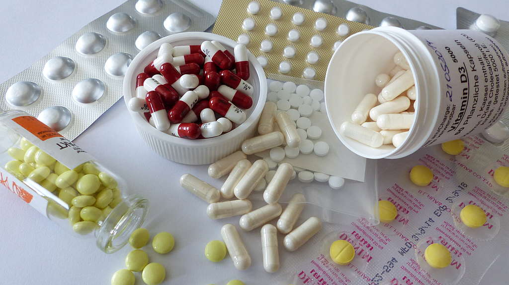 Pillen und Kapseln verschiedener Farben auf einem Tisch verstreut