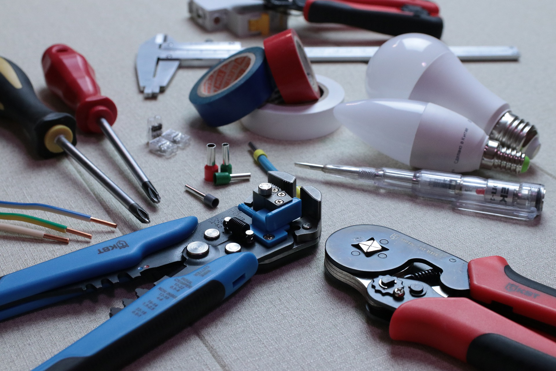 Lampen, Zange, Isolierband, Kabel, diverse Elektroartikel auf einer Unterlage verteilt